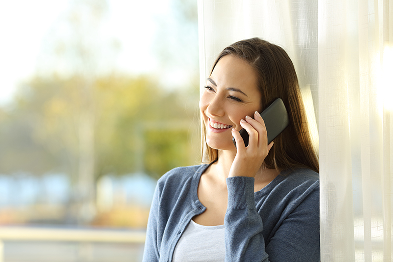 a happy woman talking on the phone