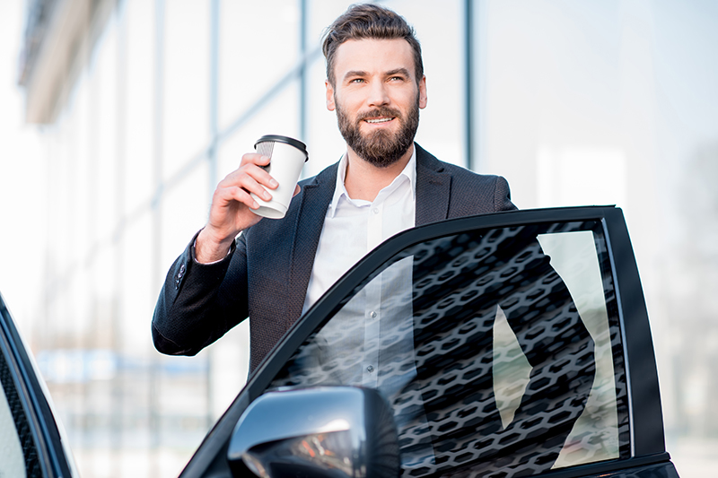 Man Drinking Coffee by Car
